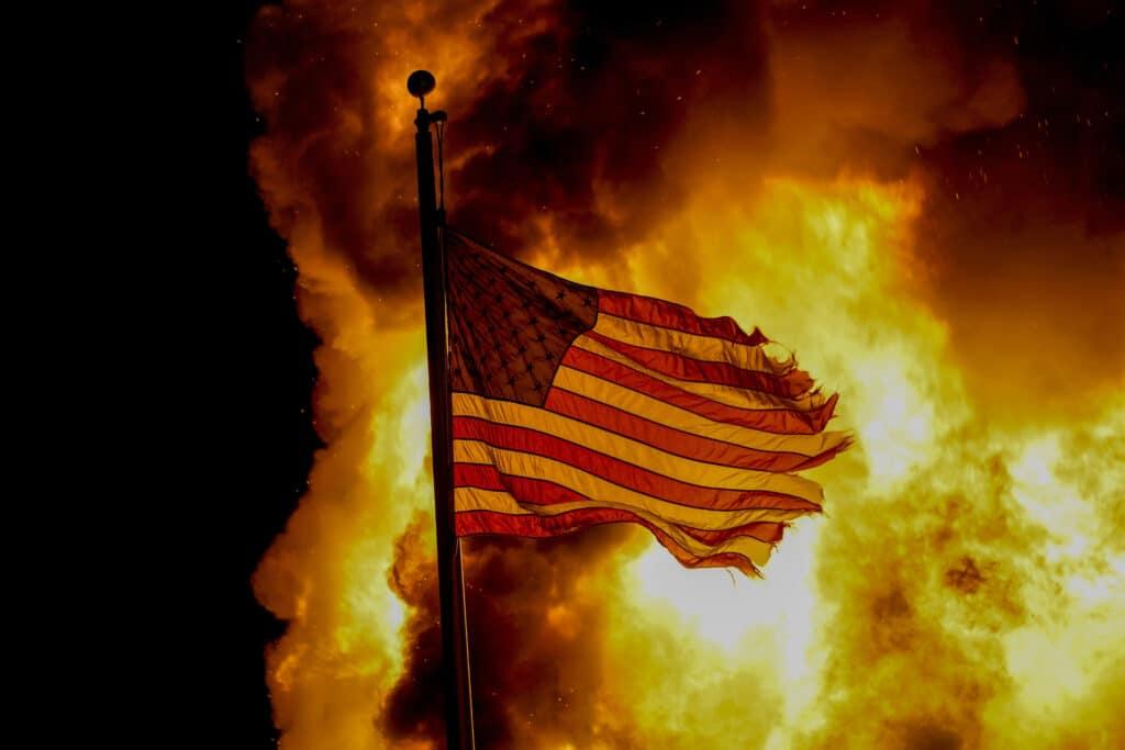 Americká zástava veje nad horiacou budovou počas protestov v meste Kenosha, v americkom štáte Wisconsin 24. augusta 2020. Foto: TASR/AP