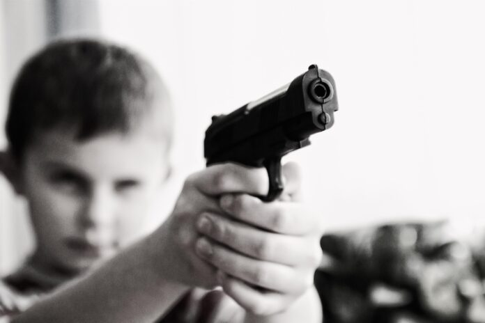 child, holding a gun, point